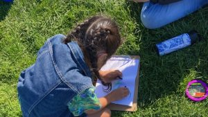 Young kid in blue jacket looks down at the grass and a clipboard as they draw what they observe around them.